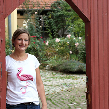 Corinna im Hoftor; Garten im Hintergrund